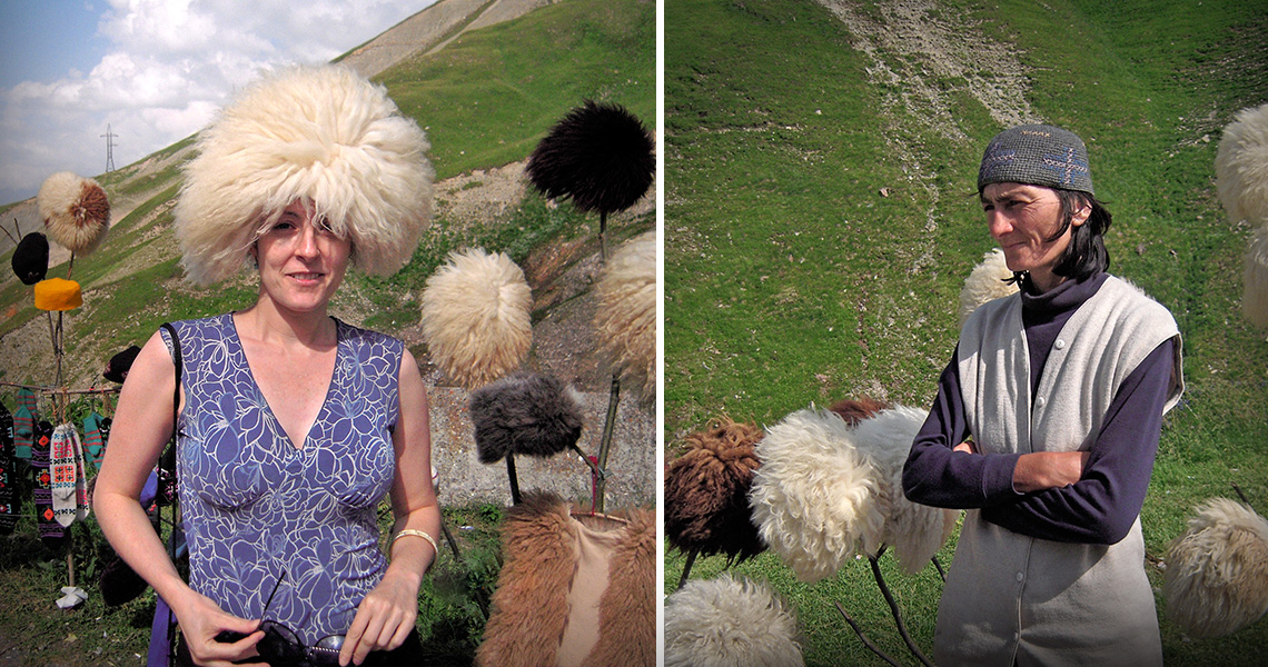 Trying on hats in the Caucasus Mountains, Georgia. The saleswoman looks on.